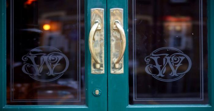 FILE PHOTO: Wetherspoon's logos are seen at the entrance to a pub in central London