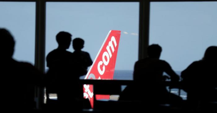 People look out at a Jet2.com aircraft from the departures area of Lanzarote Airport, in
