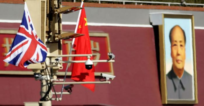 A Union flag and a Chinese flag are placed at a pole with security cameras in front of a