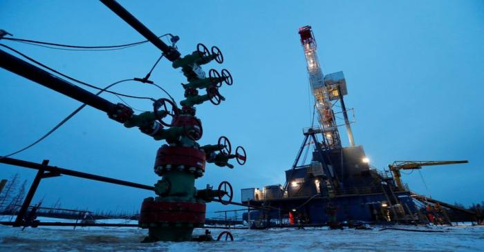 FILE PHOTO: A view shows a well head and a drilling rig in the Irkutsk Oil Company-owned