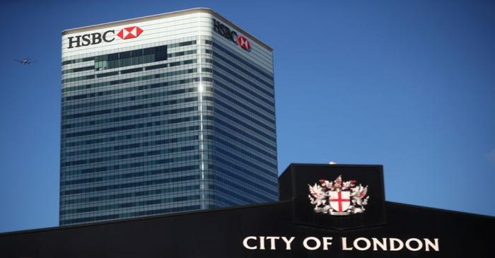 HSBC's building in Canary Wharf is seen behind a City of London sign outside Billingsgate