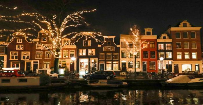 FILE PHOTO: Trees are illuminated near a canal in central Amsterdam