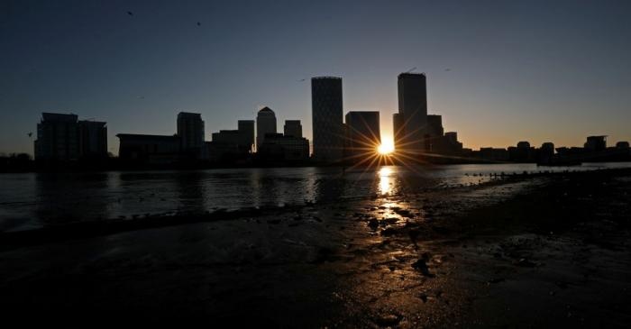 FILE PHOTO: The sun rises behind the Canary Wharf financial district in London
