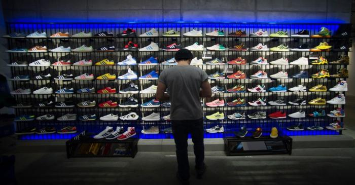 A man stands in front of a rack with Adidas Original shoes before the opening at the new Adidas