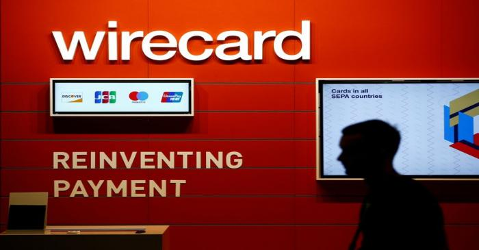 FILE PHOTO: A man walks past the Wirecard booth at the computer games fair Gamescom in Cologne,