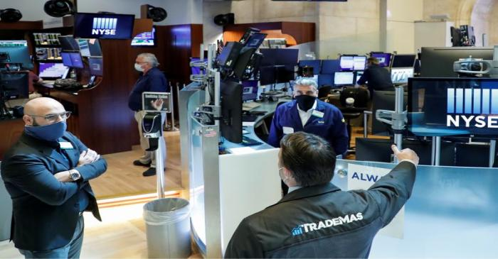 Traders wearing masks work, on the first day of in person trading since the closure during the