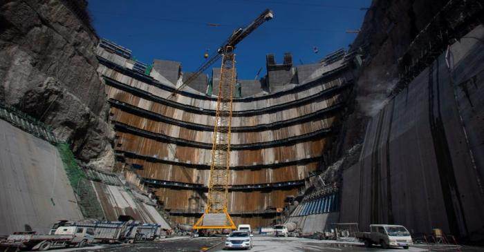 FILE PHOTO: Crane is seen near the dam of Wudongde hydropower plant under construction, on the