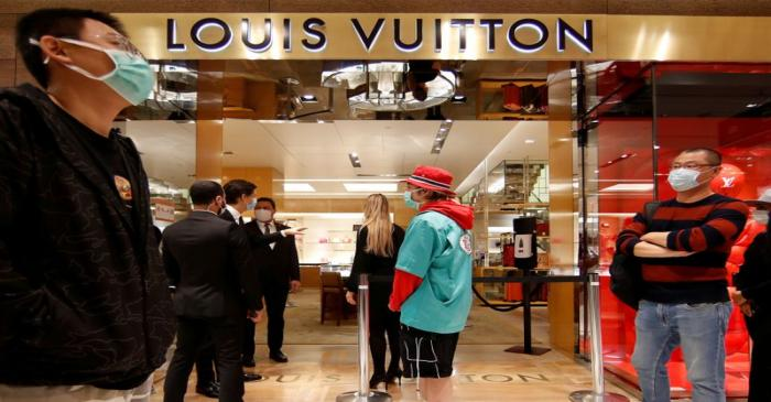FILE PHOTO: Customers stand in front of a Louis Vuitton shop inside the department store Le