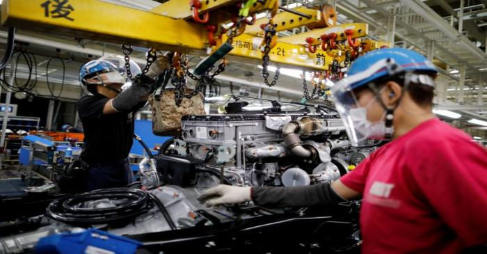 FILE PHOTO: Employees wearing protective face masks and face guards work on the automobile