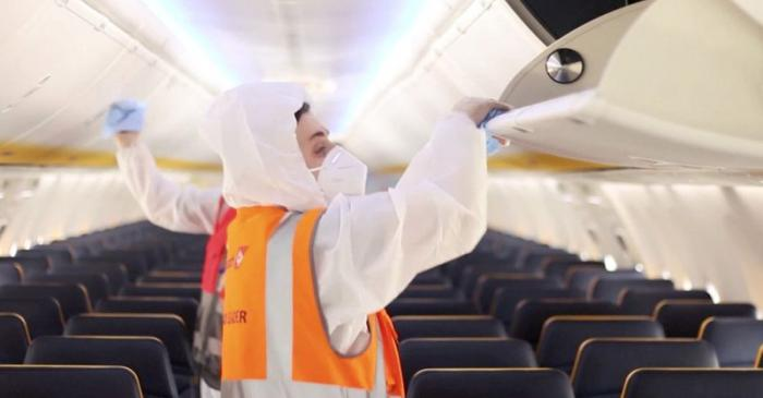 People disinfect an airplane cabin in this still image taken from a Ryanair safety video