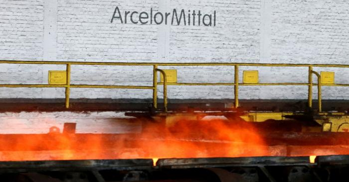FILE PHOTO: The logo of ArcelorMittal is pictured in front of heat rising from a red-hot steel