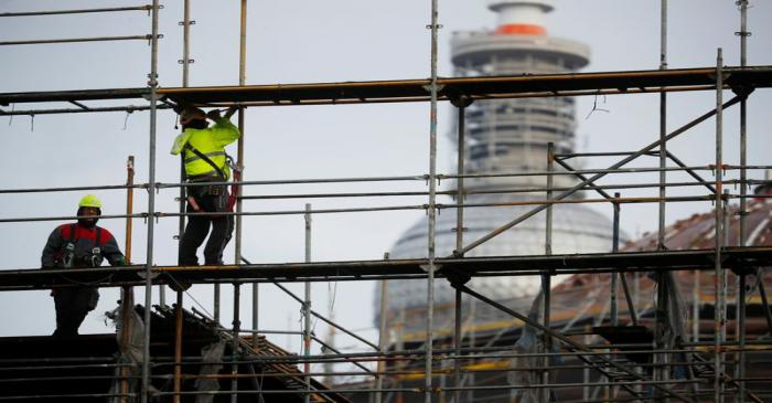 FILE PHOTO: Construction workers dismantle a scaffold in front of television tower in Berlin