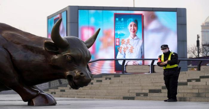 FILE PHOTO: Security guard wearing a face mask stands near the Bund Financial Bull statue and a