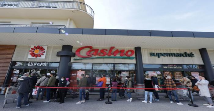 FILE PHOTO: People queue to enter a Casino supermarket in Nice