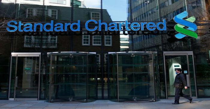 FILE PHOTO: A man walks past the head office of Standard Chartered bank in the City of London
