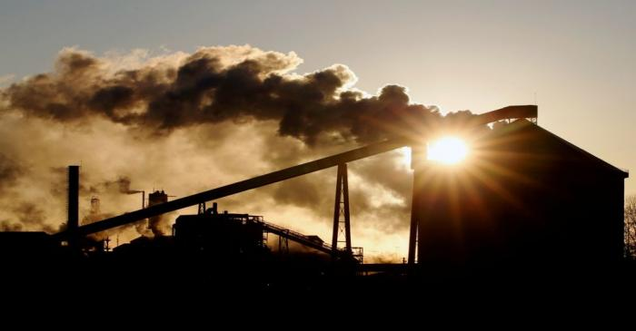 FILE PHOTO: The sun appears behind a Tereos sugar factory in Escaudoeuvres
