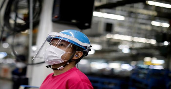 FILE PHOTO: An employee wearing a protective face mask and face guard works on the automobile