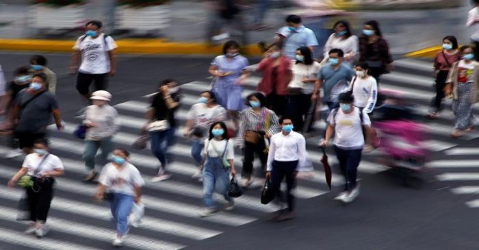 People wearing face masks walk on a street in Shanghai