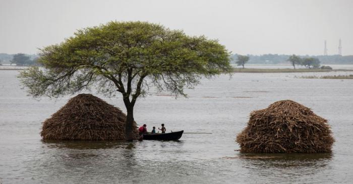 FILE PHOTO: A woman with two children rows small boat in a flooded field in Bhagalpur district