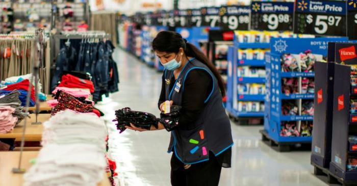 FILE PHOTO: A worker is seen wearing a mask while organizing merchandise at a Walmart store, in