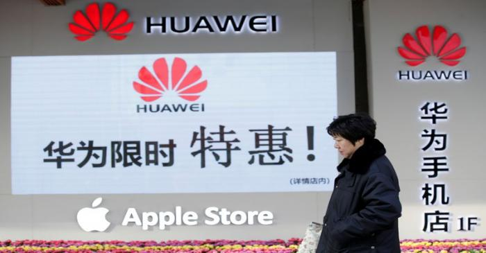 Woman walks past a Huawei and Apple shops in Beijing