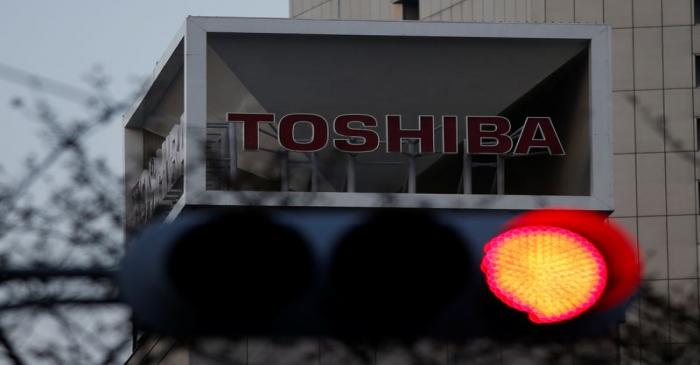 FILE PHOTO: The logo of Toshiba Corp is seen behind a traffic light at the company's