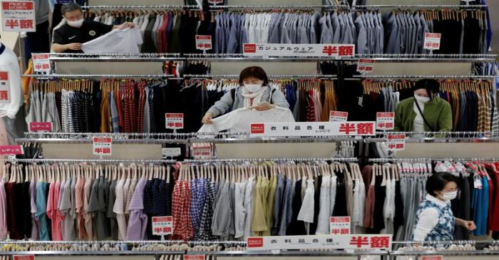 FILE PHOTO: Shoppers wearing protective masks choose clothes at Japan's supermarket group
