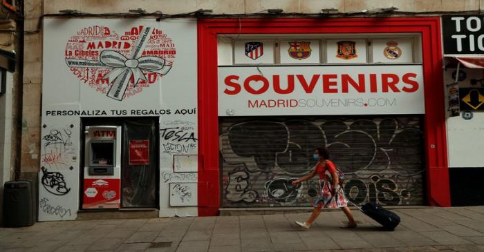 FILE PHOTO: A woman wearing a protective face mask walks past a closed souvenirs store, amid