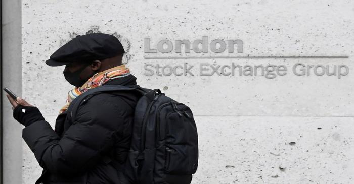 FILE PHOTO: A man wearing a protective face mask walks past the London Stock Exchange Group