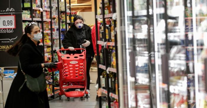 FILE PHOTO: People wearing protective face masks are seen in a supermarket in Posillipo