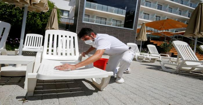 FILE PHOTO: Worker cleans a sunbed in a pool area of a hotel, in Palma de Mallorca