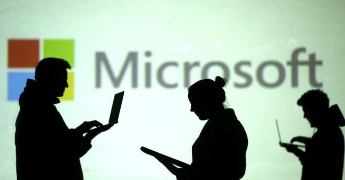 Silhouettes of laptop users are seen next to a screen projection of Microsoft logo in this