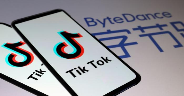 FILE PHOTO: TikTok logos are seen on smartphones in front of displayed ByteDance logo in this