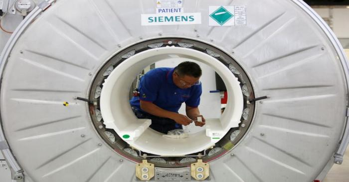 A staffer works on a magnetic resonance imaging machine at a production line of Siemens