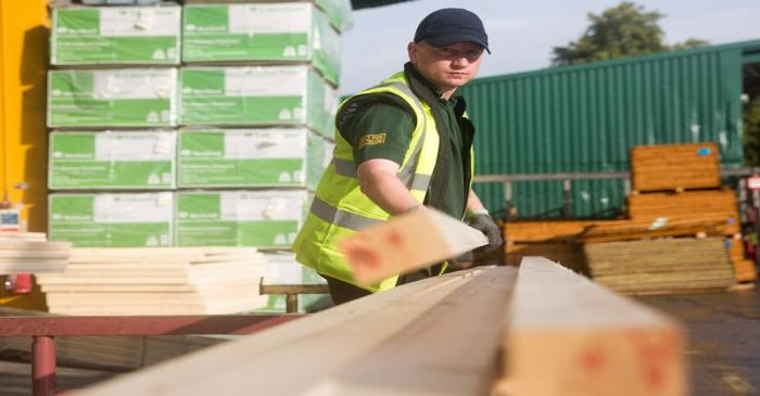 File photo of a worker stacking timber at the Vauxhall depot of building material supplier