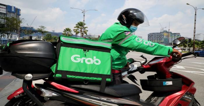 FILE PHOTO: A GrabFood rider gets ready for a delivery outside a shopping mall, amid the