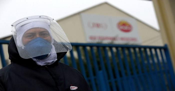 An employee of the JBS SA poultry factory wears a protective mask after the company was hit by