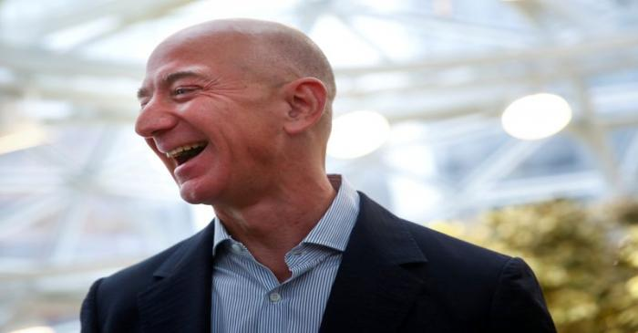 FILE PHOTO: Amazon founder and CEO Jeff Bezos laughs as he talks to the media while touring the
