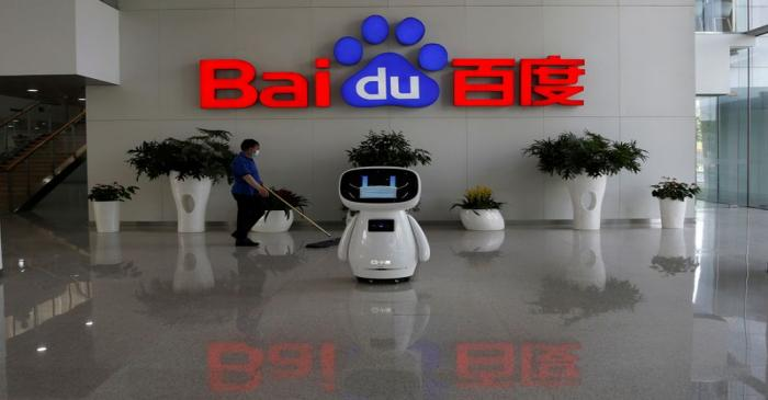 FILE PHOTO: A worker wearing a face mask cleans the floor, near a Baidu AI robot which shows a