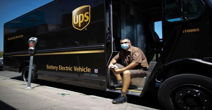 UPS Driver Gilbert Lopez poses with his electric UPS truck, amid the global outbreak of the