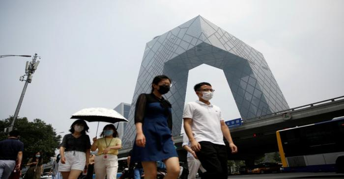 People wearing face masks walk past the CCTV headquarters in Beijing