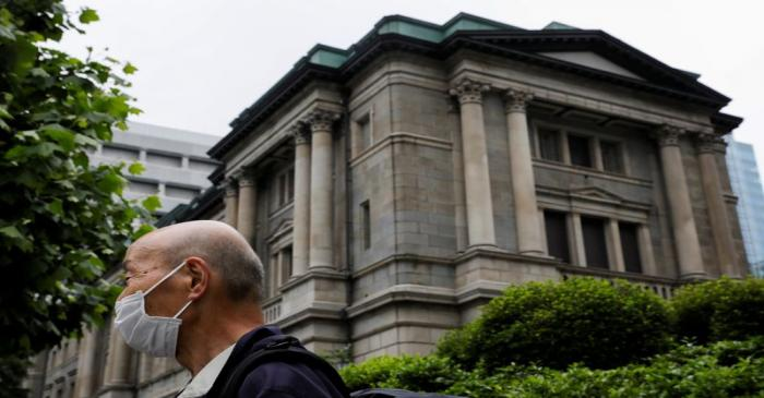A man wearing a protective mask stands in front of the headquarters of Bank of Japan amid the