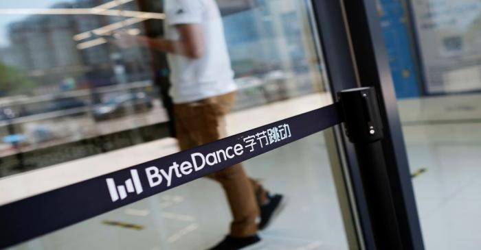 FILE PHOTO: Man walks by a logo of Bytedance, which owns short video app TikTok, at its office