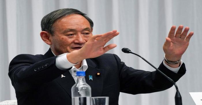 FILE PHOTO: Japan's Chief Cabinet Secretary Yoshihide Suga waves after a debate for the ruling