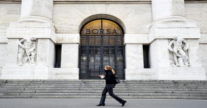 FILE PHOTO: Woman goes past the Italian Stock Exchange in Milan