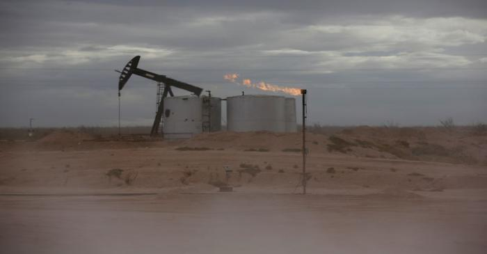 FILE PHOTO: Dust blows around a crude oil pump jack and flare burning excess gas at a drill pad