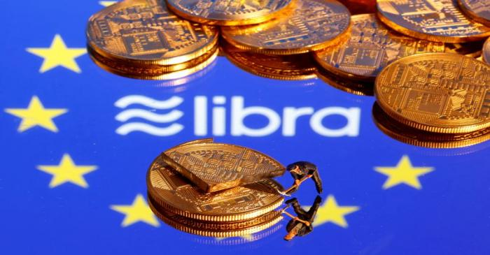 FILE PHOTO: A small toy figure is seen on representations of the virtual currency on a