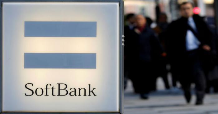 People walk behind the logo of SoftBank Corp in Tokyo