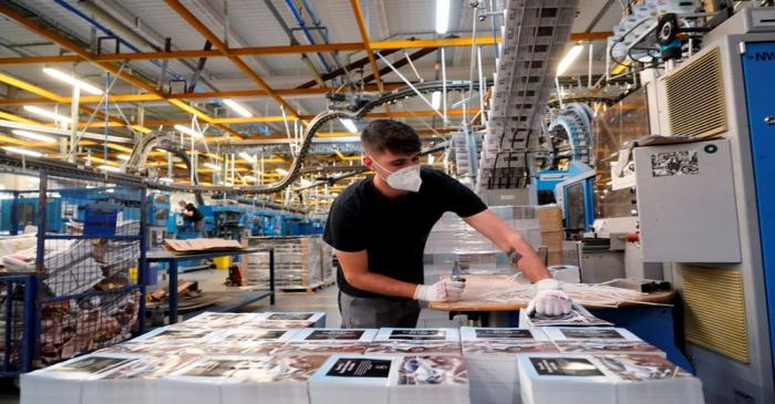 A man wearing a protective face mask works at a printing press amid the coronavirus disease