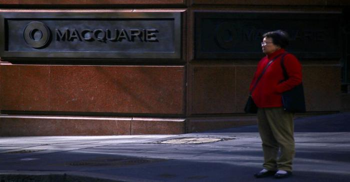 A pedestrian stands near the logo of Australia's biggest investment bank Macquarie Group Ltd